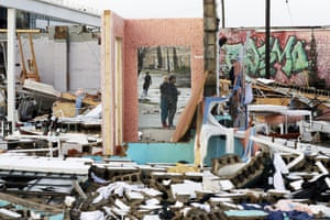 People are reflected in a mirror of a destroyed building.