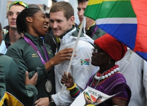 Semenya shares a joke with fellow medallist Cameron van der Burgh as her grandmother Mmabuthi Segale looks on as the team is mobbed by fans at the airport.