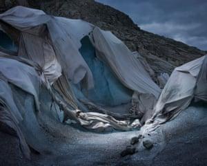 Shroud, 2018, bởi Simon Norfolk và Klaus Thyman: trong nỗ lực bắt giữ sự tan chảy của băng tại một điểm thu hút khách du lịch băng tại Rhône Glacier, các doanh nhân Thụy Sĩ địa phương đã trả tiền để được phủ lên một tấm chăn nhiệt. Chúng tôi đã chọn tiêu đề, nói rằng Norfolk, 'bởi vì có vẻ như họ đã tạo ra một tấm vải liệm cho cái chết của sông băng.
