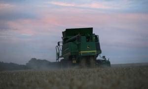 A John Deere combine harvester is seen harvesting winter wheat in a field near Kimpton