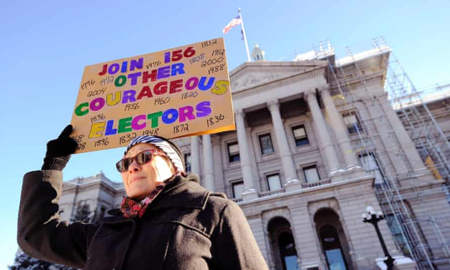 Amber Dahlin holds a sign urging the electors to vote their conscience outside the Colorado capitol building in Denver on Monday.