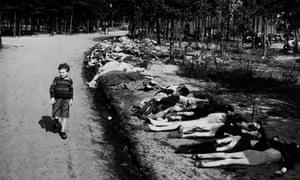 A young survivor walks along a road lined by the corpses of hundreds of prisoners who died at the Bergen-Belsen camp, in May 1945.