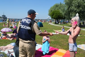 An officer from the Ministry of Emergency Situations distributes leaflets with safety guidelines to people on Pirogovo beach on the Klyazma reservoir