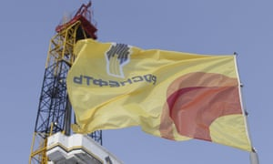 A flag with the logo of Russian oil firm Rosneft flies next to an derrick at the Suzunskoye oil field in central Russia.