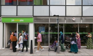 People queue to enter a job centre in east London.
