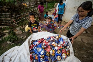Women and children crush cans for recycling