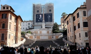 Tourists stand in front of the Spanish Steps in Rome