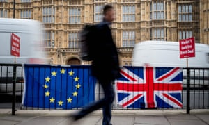 A pedestrian walks past EU and British Flags on railings outside the Houses of Parliament