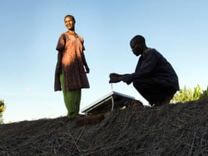 Emily Kamwendo and Stefano Simion maintain solar panel on roof in Malawi