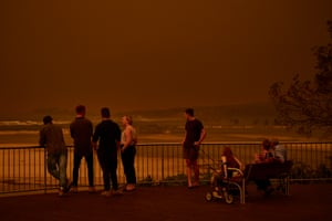 Residents look out over the beach as thick smoke covers the skyline in Tuross Head, Australia, in January as bushfires rage across the continent.