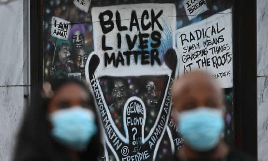 Two people watch on during a demonstration in Black Lives Matter Plaza in Washington DC in November 2020.