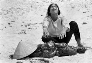 A woman mourns over the body of her husband after identifying him by his teeth and covering his head with her conical hat. The man's body was found with forty-seven others in a mass grave near Hue, April 11, 1969