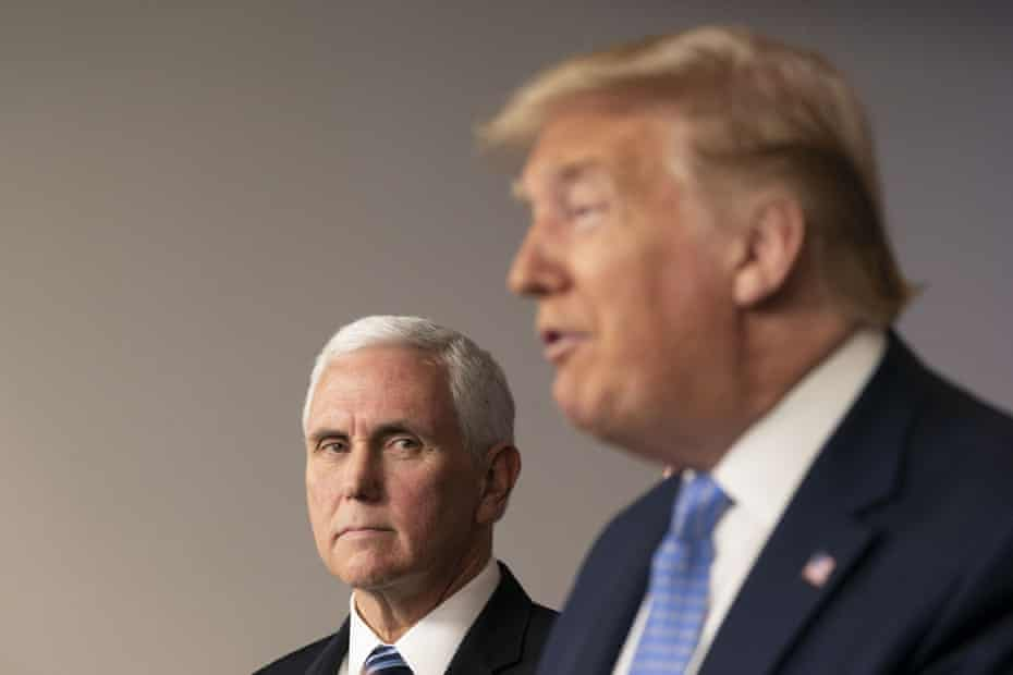 Mike Pence listens as Donald Trump, right, speaks during a news conference in the press briefing room of the White House in Washington DC.