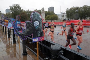 Runners pass by cardboard cut-outs depicting previous fun-runners.
