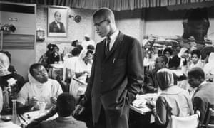 Malcolm X talking to women inside a restaurant in Harlem, New York.
