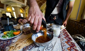 Waiter serving lunch, Iranian style, pouring dizi stew into a bowl.