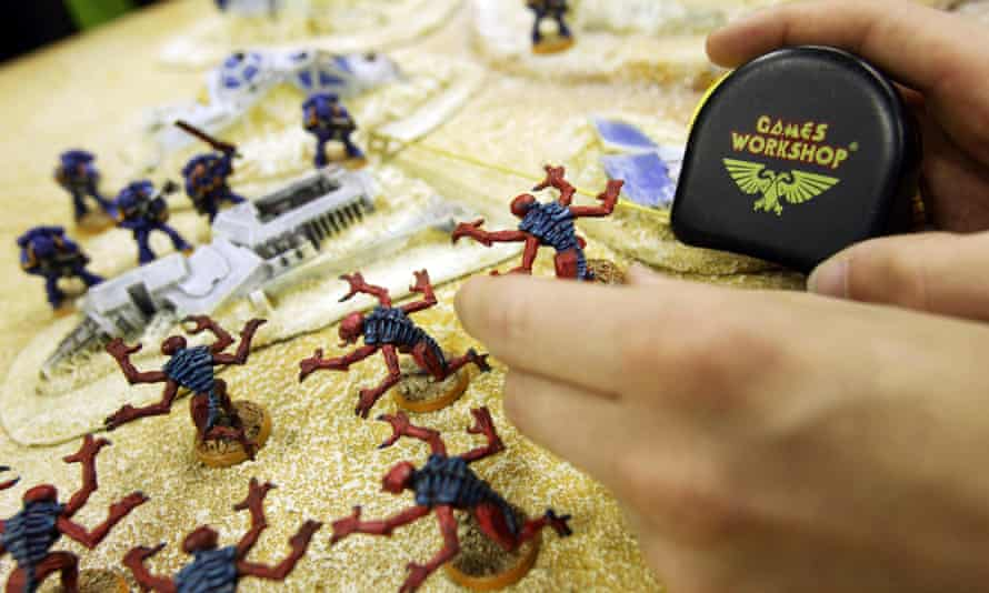 A customer plays a game of Warhammer in a Games Workshop store.