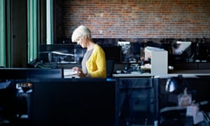 Mature businesswoman standing at workstation