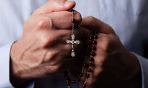 Someone holds  a rosary with a Crucifix