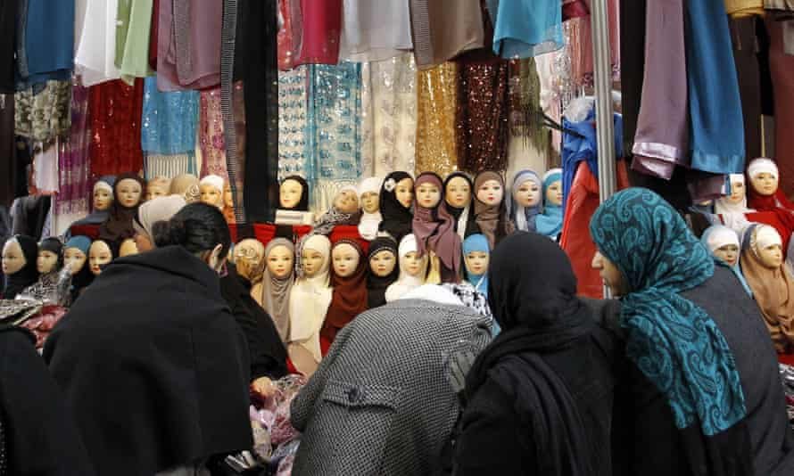 Women look at veils on display at an exhibition hall for the Muslim World Fair in Le Bourget, outside Paris
