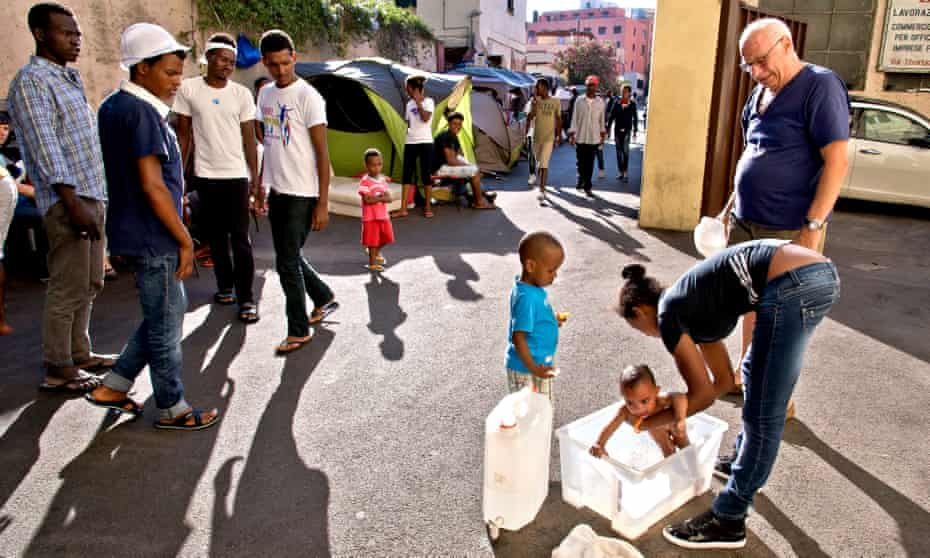An Eritrean mother in Rome tries to bathe her daughter in the city's migrant camp.