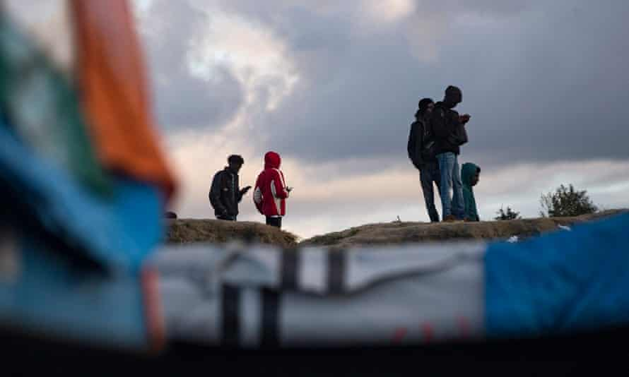Refugees stand atop a small hill in the camp in Calais, northern France, which will be dismantled over the coming week.