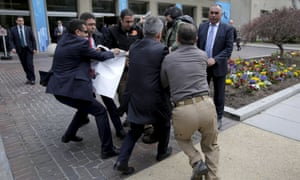 Turkish security struggle to take a sign away from protesters in front of the Brookings Institute.