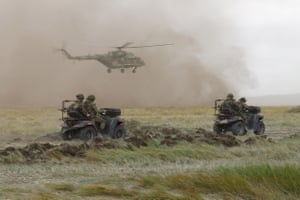 Military personnel drive Russian A-1 quadricycles as a helicopter takes off