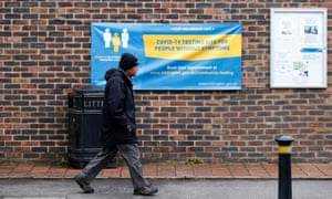 A man walks past a banner of a coronavirus testing site in Hillingdon, England.