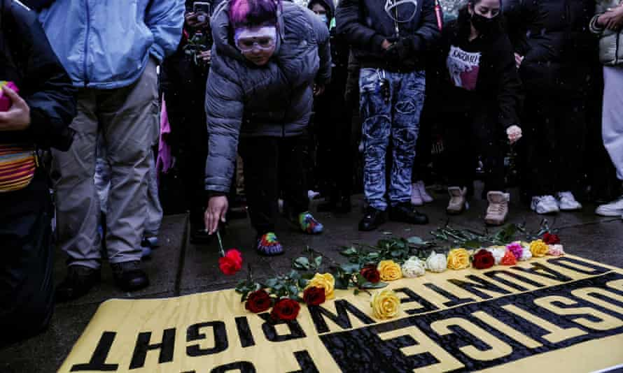 People lay flowers on a sign as they rally outside the Brooklyn Center police department, days after Daunte Wright was shot and killed by a police officer in  Minnesota.