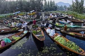 Kashmiri men gather with their boats laden with vegetables at the floating vegetable market on Dal Lake at dawn in Srinagar