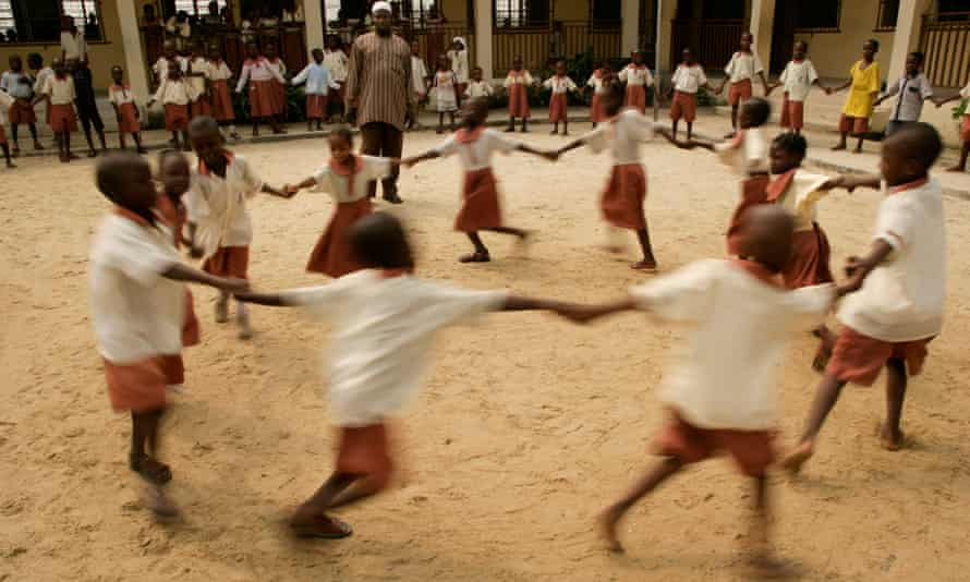 Children dance in a circle during break time at a primary school in Lagos.