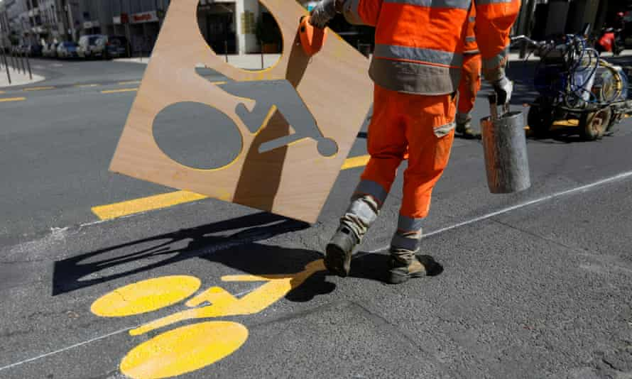 A worker paints a sign representing a cyclist on a new cycling path in Vincennes near Paris