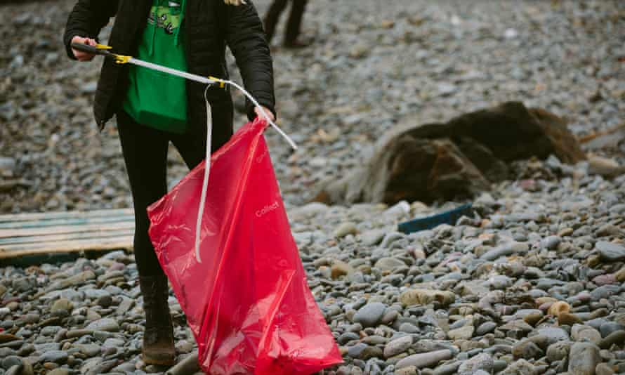 Woman collecting rubbish from pebble beach