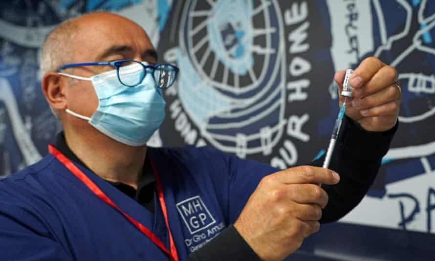 Doctor Gino Amato prepares to administer a dose of the Pfizer/BioNTech covid-19 vaccine at a vaccination centre set up at Tottenham Hotspur's football stadium in London on 20 June.