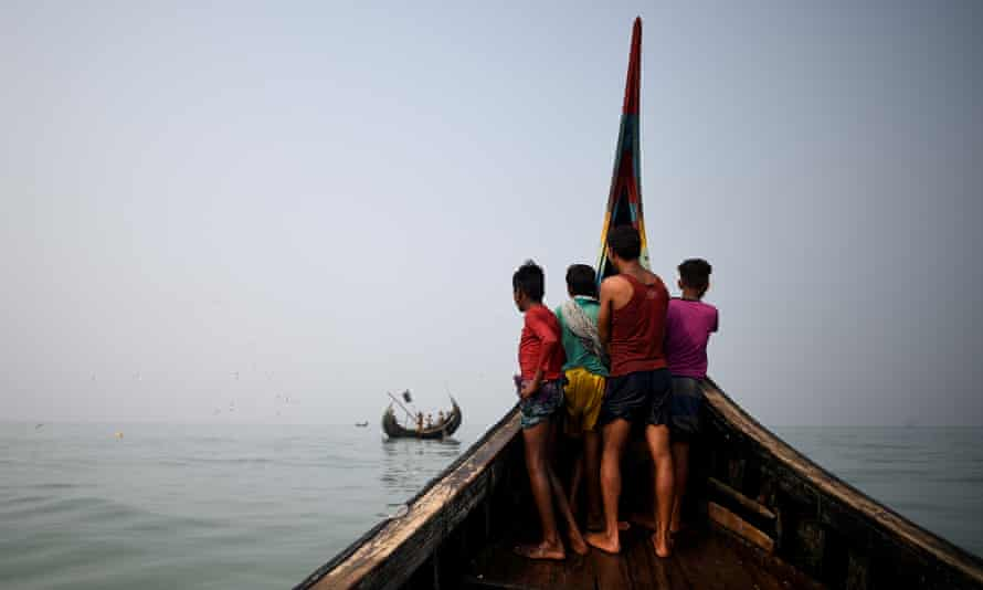 Rohingya refugees crew a fishing boat in the Bay of Bengal