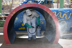 A Las Vegas maintenance worker disinfects playground equipment.