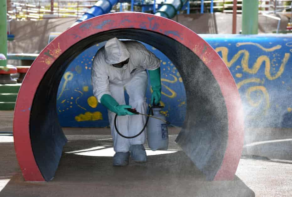 A Las Vegas maintenance worker disinfects playground equipment.