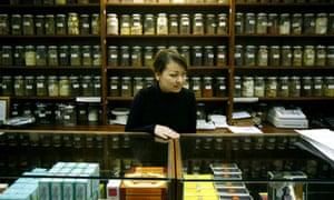 A herbalist with jars of herbal medicine at Oriental City, Colindale, London.