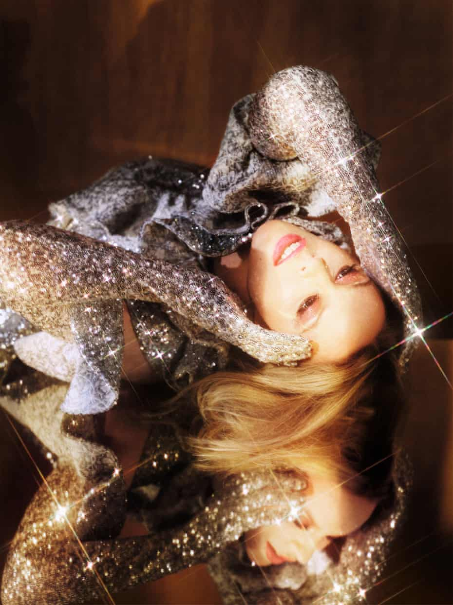 Kylie Minogue lying down in a very glittery silver outfit