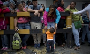 A mother and son wait to buy food outside a supermarket in Caracas, Venezuela.