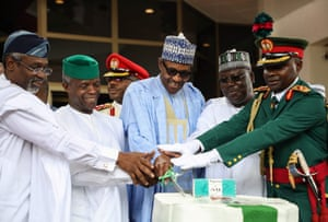 (From left) The speaker of the House of Representatives Femi Gbajabiamila, vice-president Yemi Osinbajo, president Muhammadu Buhari and senate president Ahmed Lawan get a bit of military assistance cutting an anniversary cake during a ceremony marking 60 years of independence from the UK, on 1 October 2019.