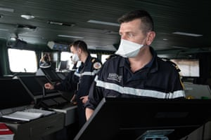 A photo circulated by the French defence ministry shows sailors wearing protective face masks on board the aircraft carrier Charles de Gaulle