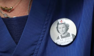 """A Belgian healthcare worker wears a badge reading """"Get inoculated."""""""