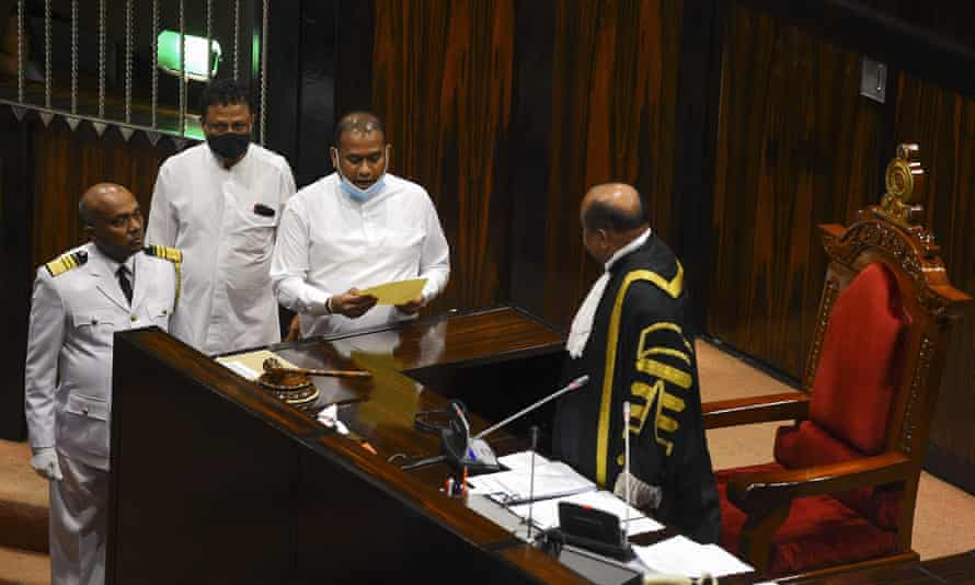 Premalal Jayasekara reading the oath surrounded by three men, one in black and gold robes
