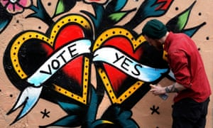 A graffiti artist finishes a Yes campaign piece in central Dublin in Ireland on Wednesday.