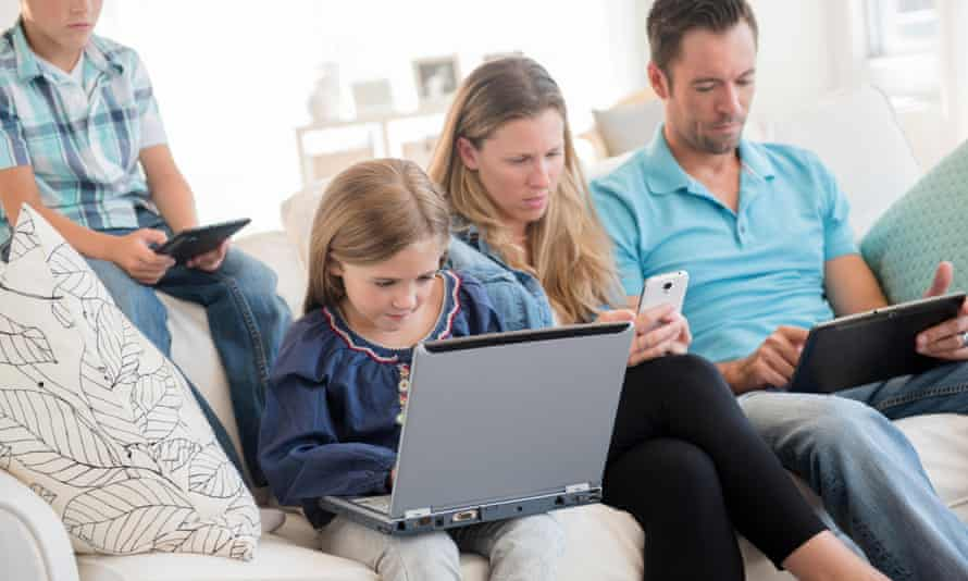 A family using phones, laptops and tablets at home