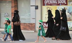 Saudi women and their children walk along a street in Riyadh