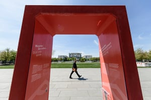 A pedestrian passes a red gate in front of the German chancellery in Berlin, Germany. The concrete gate has been installed to mark 500 years since the start of the Reformation