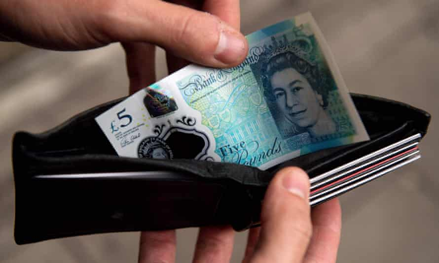 A person holding a wallet containing a £5 note